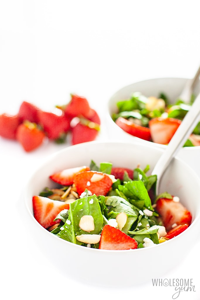 two bowls of salad with strawberry spinach salad dressing