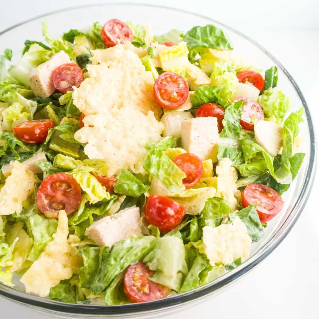 This delicious low carb Caesar salad features crunchy parmesan crisps, chicken, and creamy homemade Caesar dressing. Just 10 ingredients including dressing!