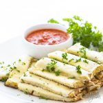 stack of cheesy cauliflower breadsticks with marinara