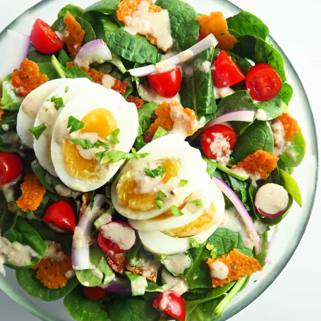 This delicious spinach bacon salad recipe is brimming with crunchy cheddar cheese crisps, crisp spinach, juicy tomatoes, and smoky bacon dijon dressing.