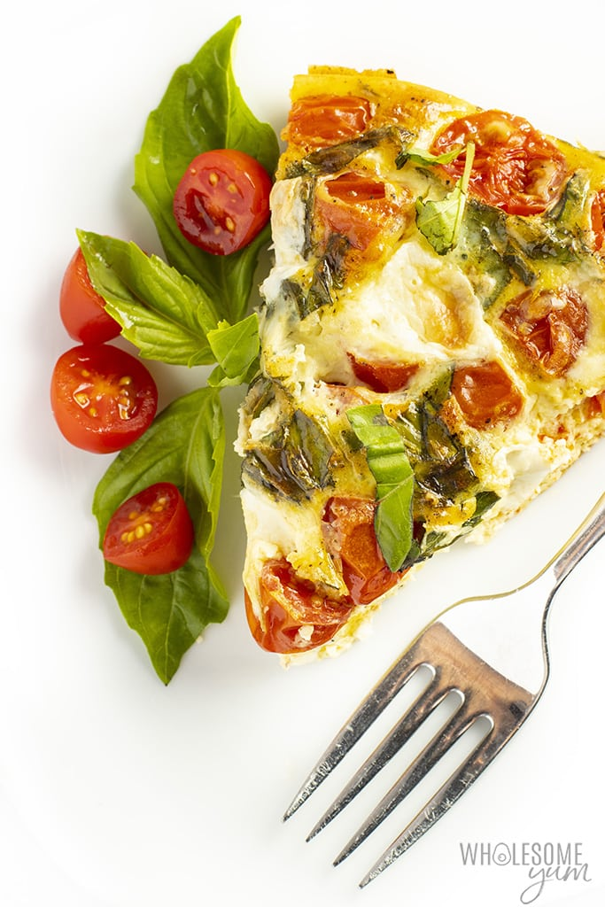 Slice of crustless quiche with tomatoes, basil and a fork