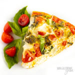 Slice of crustless quiche with tomatoes and basil on a plate