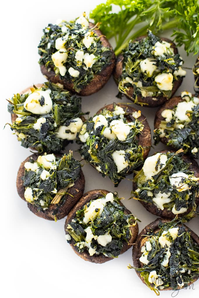 Lots of spinach and feta cheese stuffed mushrooms arranged together