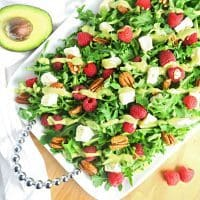 This colorful raspberry salad recipe with brie, pecans, and creamy avocado dressing is ready in just five minutes. Low carb and gluten-free.