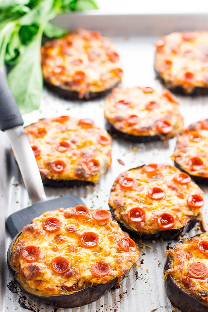 Eggplant Pizzas on a pan with one being served with a spatula