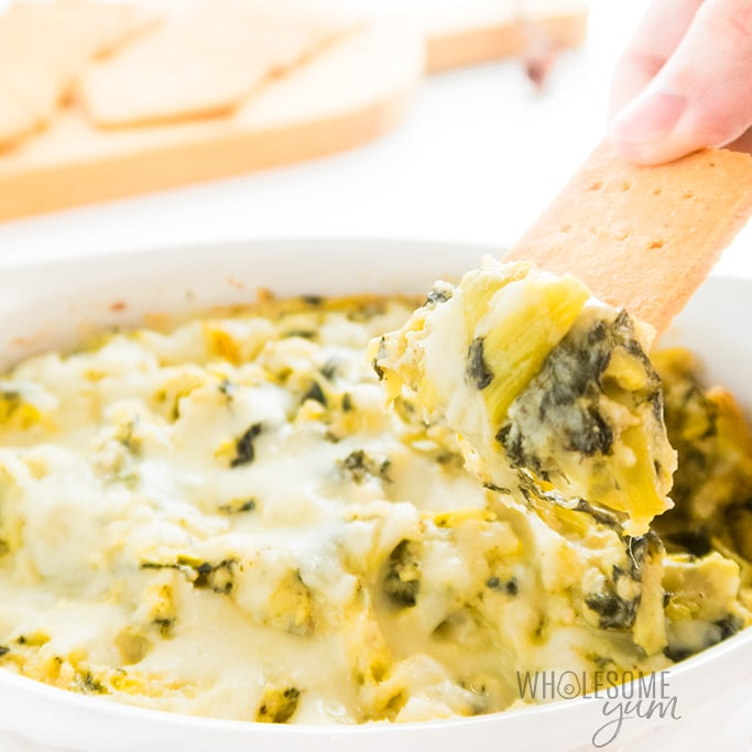 keto spinach artichoke dip with a cracker dipping into it