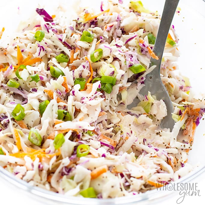 Keto coleslaw in bowl with spoon and green onions