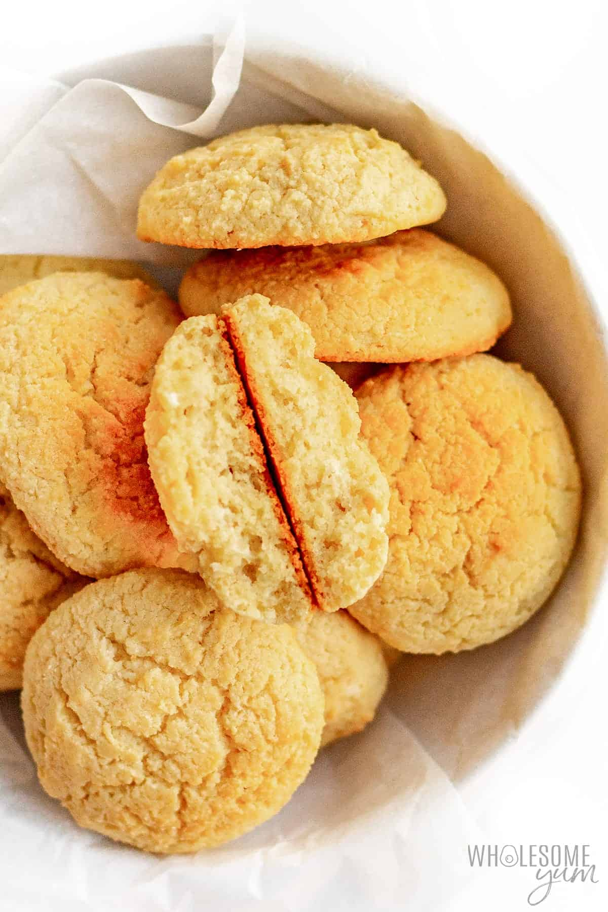 Buttery almond flour biscuits in a bowl, showing the inside of one biscuit