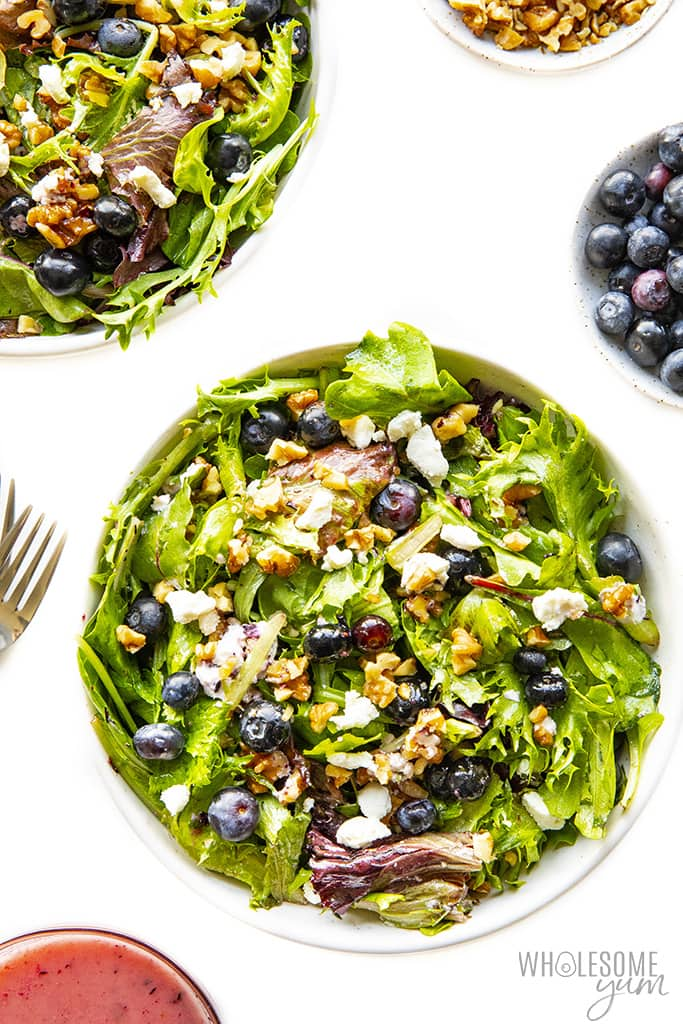 Bowl of spring mix salad with toppings and dressing