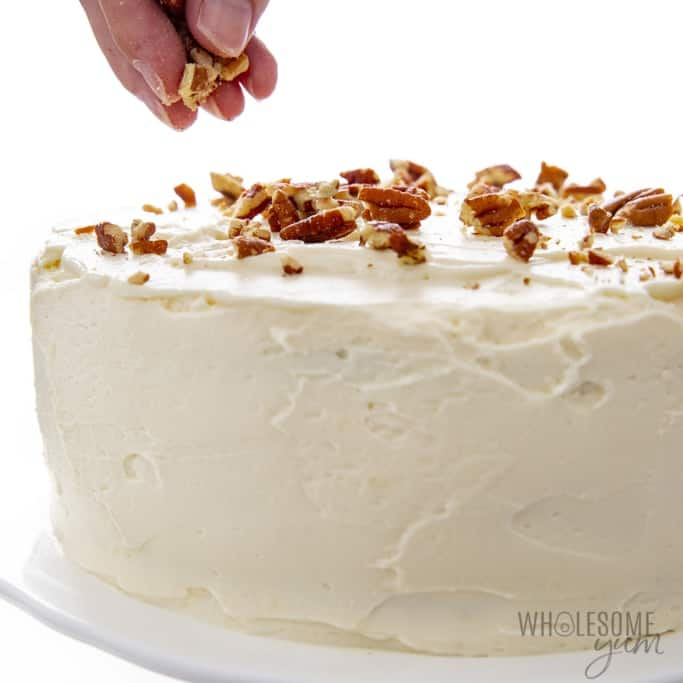 Adding topping to frosted keto birthday cake