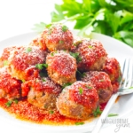 Pile of low carb keto meatballs with marinara sauce and cheese, on a plate
