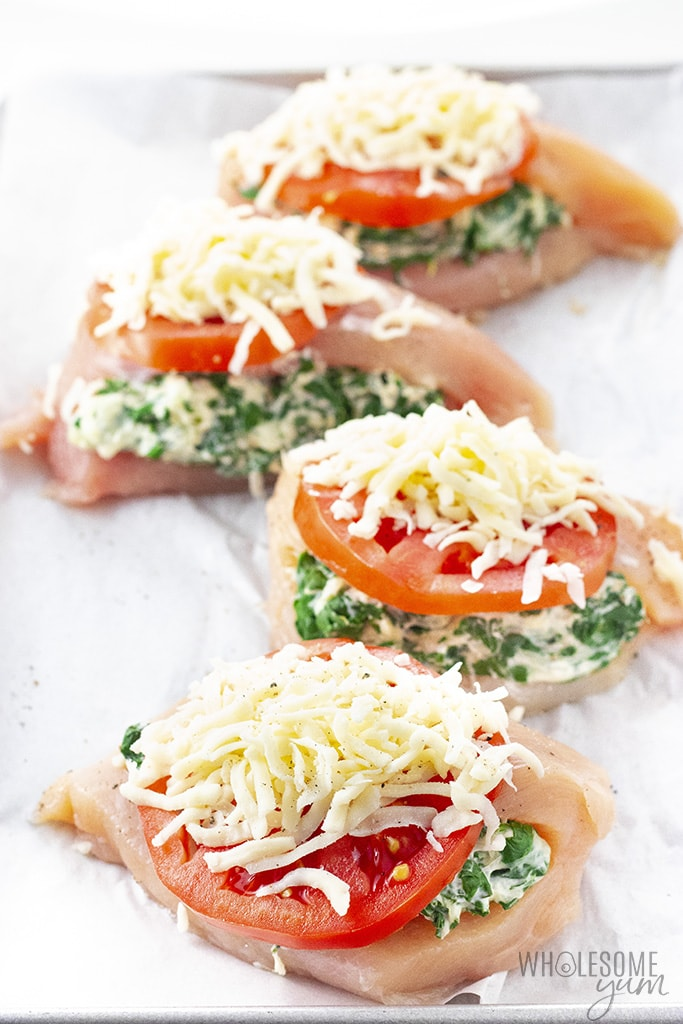 Raw stuffed chicken breast with sliced tomato and cheese on a pan