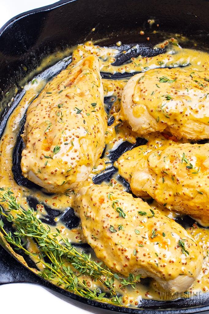 A few pieces of creamy mustard chicken in a skillet