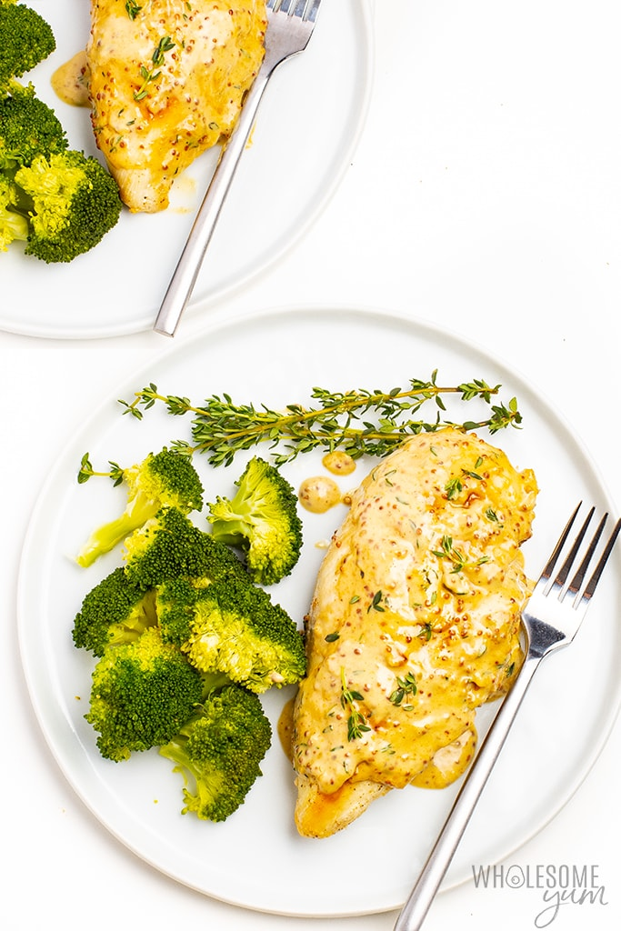 Chicken with mustard cream sauce and broccoli on 2 plates