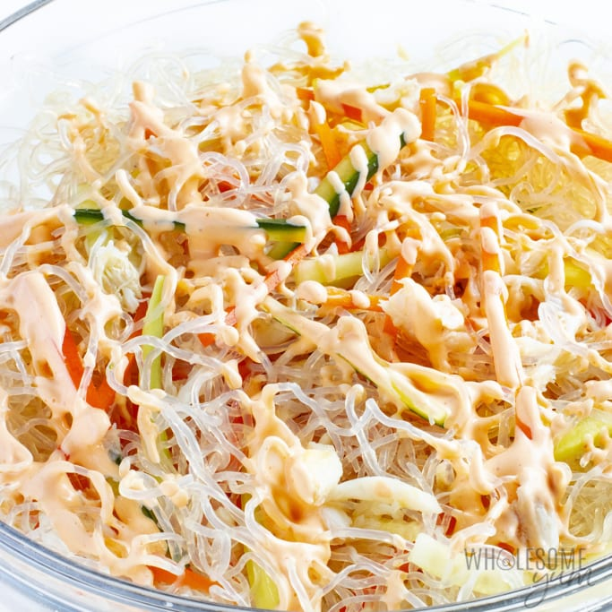 kani salad ingredients with dressing poured on top