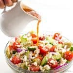 Mediterranean Salad Recipe in bowl with dressing pouring