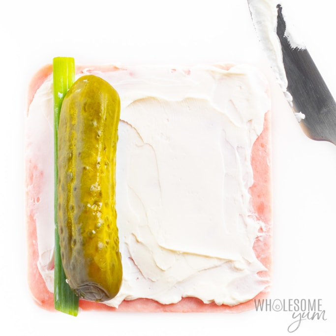 Assembling dill pickle roll ups with ham and cream cheese