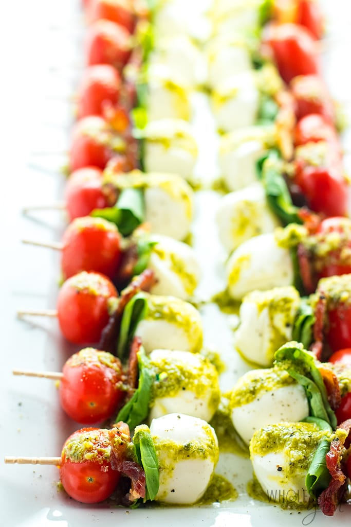 mini Caprese skewers on a platter with pesto sauce
