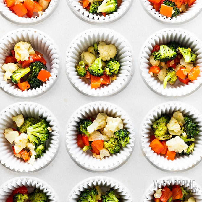 Muffin tins filled with roasted vegetables for egg muffins