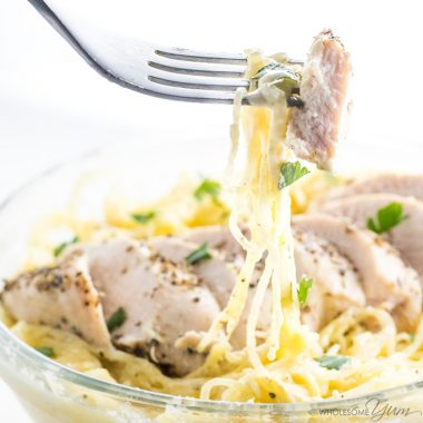 chicken alfredo in a bowl being picked up with a fork to eat