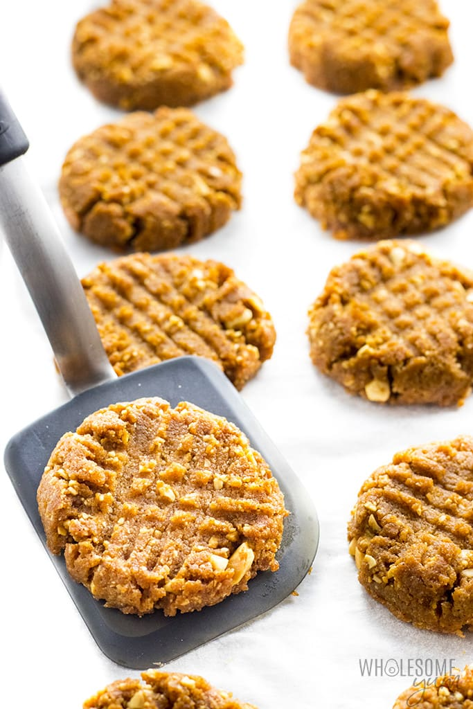 Low carb peanut butter cookies on a baking sheet with a cookie spatula