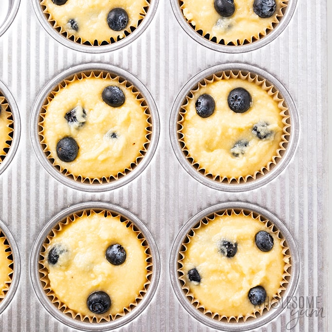 Batter for low carb muffins with almond flour and blueberries in muffin tin