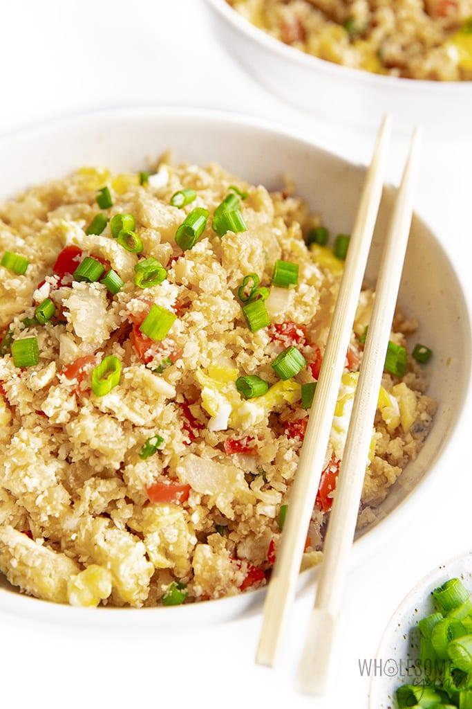 Keto cauliflower fried rice served in a bowl with chopsticks