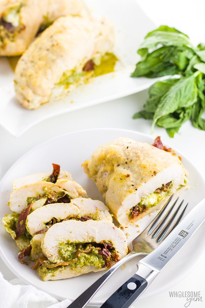 Baked Pesto Stuffed Chicken Breast with Bacon Recipe - This easy recipe makes the juiciest pesto stuffed chicken breast with bacon, mozzarella and sun-dried tomatoes. It's the best way to make baked pesto chicken!