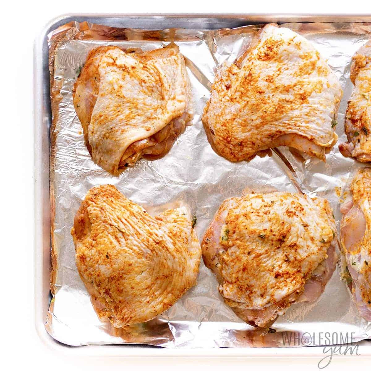 Seasoned chicken thighs on baking sheet