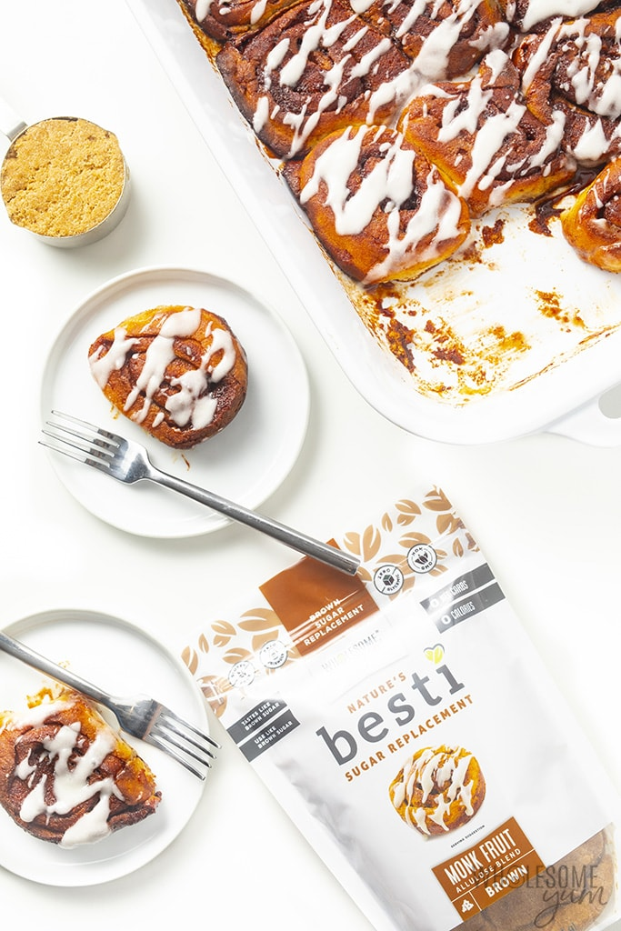 Low carb cinnamon rolls on two plates and in a baking dish, with keto brown sweetener