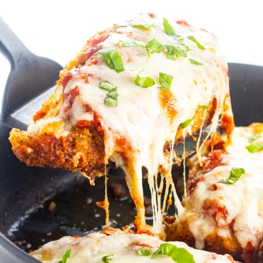 keto chicken parmesan in a pan with one chicken breast on a spatula being removed from the pan