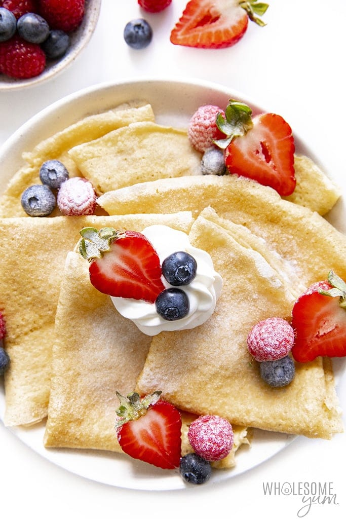 Keto crepes plated with berries and powdered sweetener