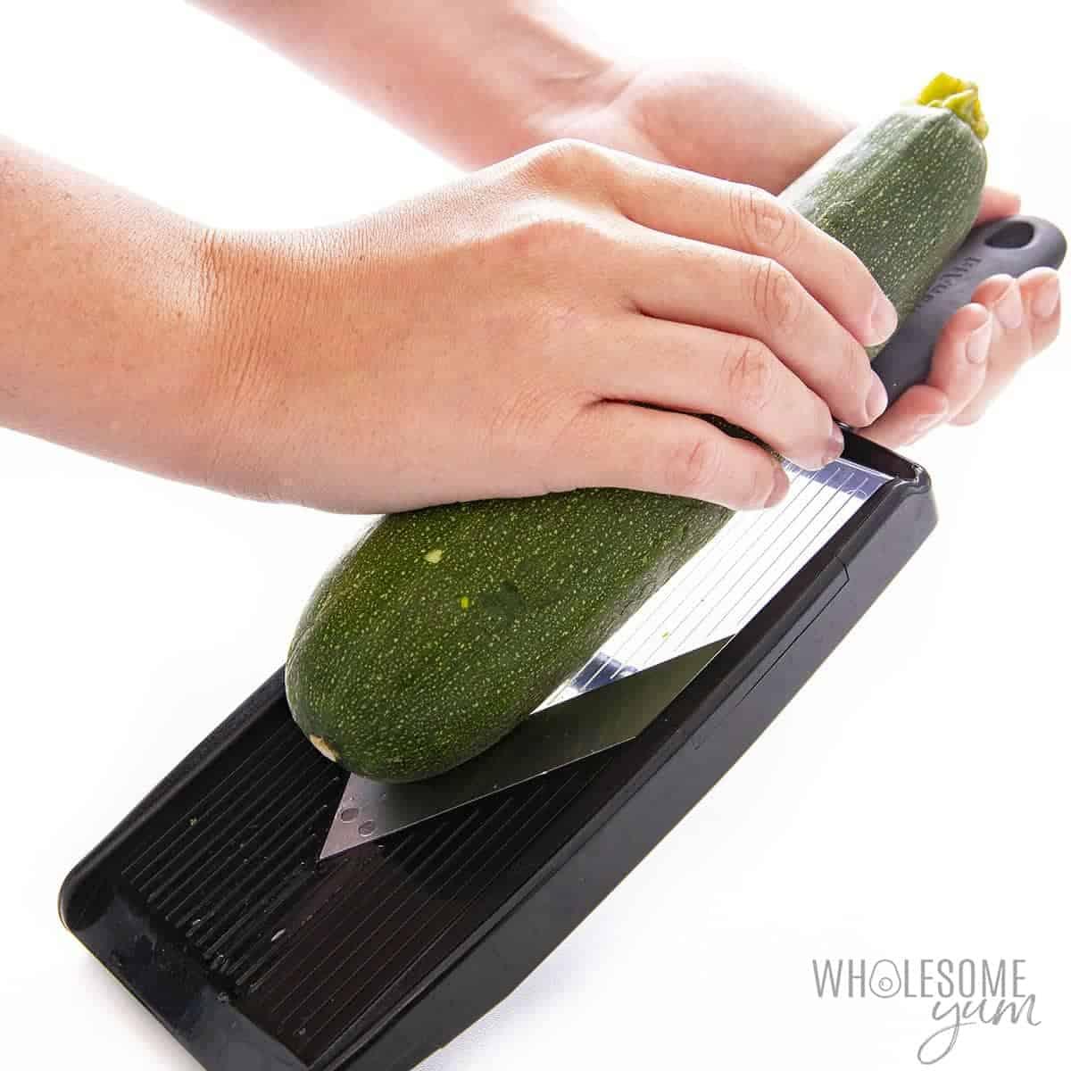 Slicing zucchini with mandoline