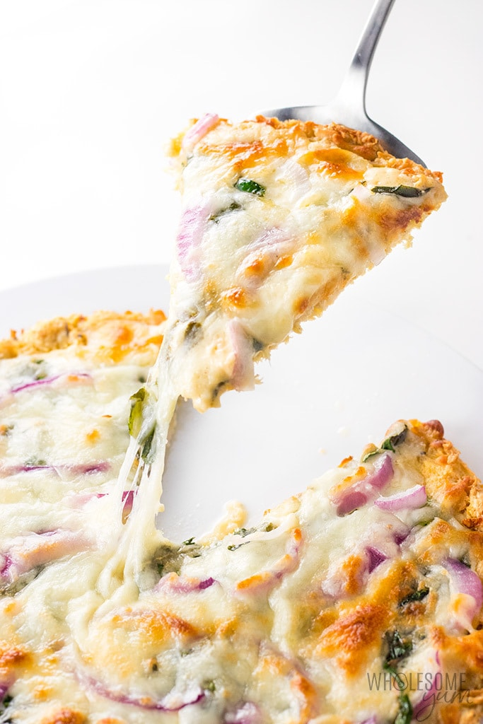 Low Carb Keto Chicken Crust Pizza Recipe - A low carb keto chicken crust pizza recipe with just 4 ingredients! Top it with creamy alfredo sauce, spinach, onions and mozzarella for a delicious and simple low carb dinner.