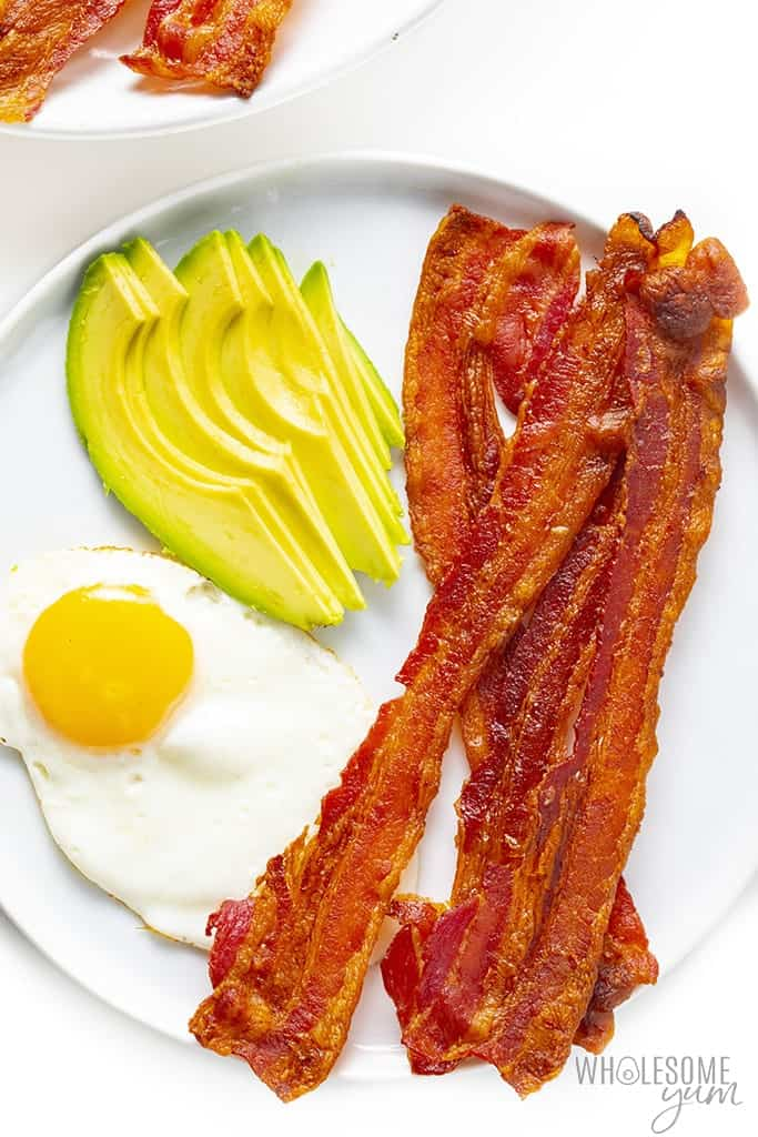 Oven baked bacon on a plate with fried egg and avocado