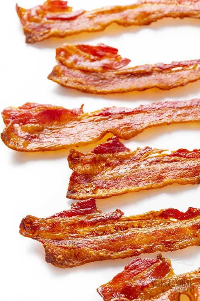 Slices of bacon baked in the oven, on a white surface