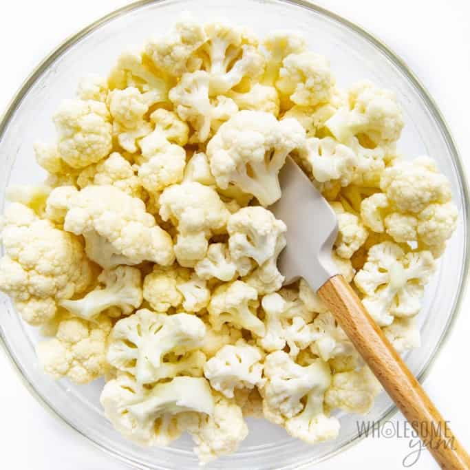 Cauliflower florets in a bowl with olive oil, salt, and pepper