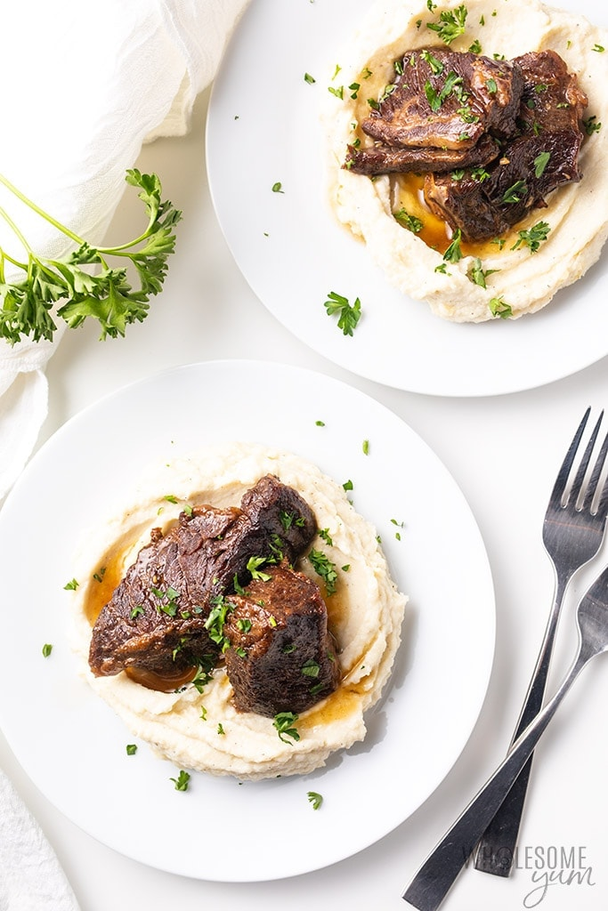beef short ribs on plates with cauliflower mash