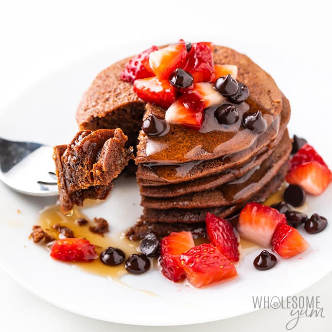 stack of chocolate protein pancakes with strawberries and chocolate chips