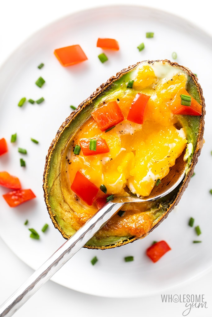 Avocado stuffed with egg with a spoon