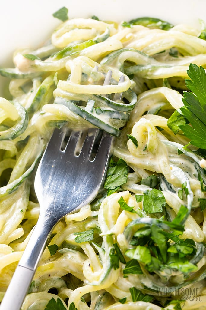 cucumber noodle salad with tahini sauce twirled on a fork