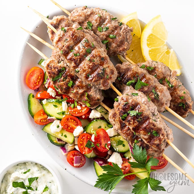Lamb kofta kebabs on plate with Greek salad
