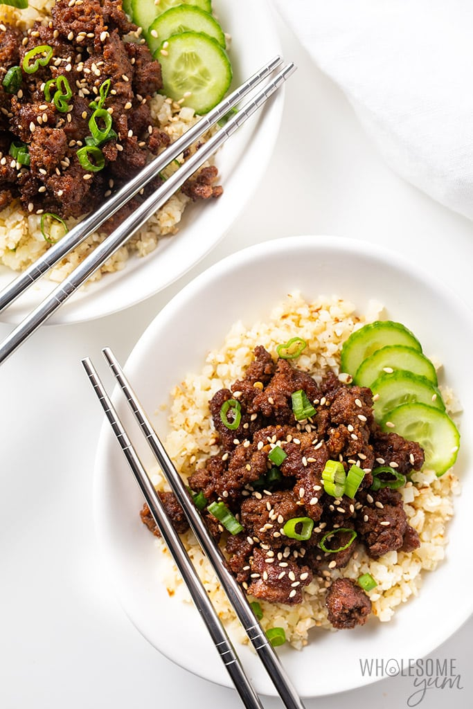 easy korean beef over cauliflower rice on white plates
