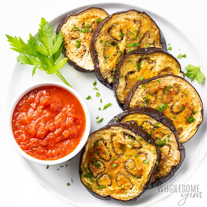 roasted eggplant slices on a plate with marinara sauce