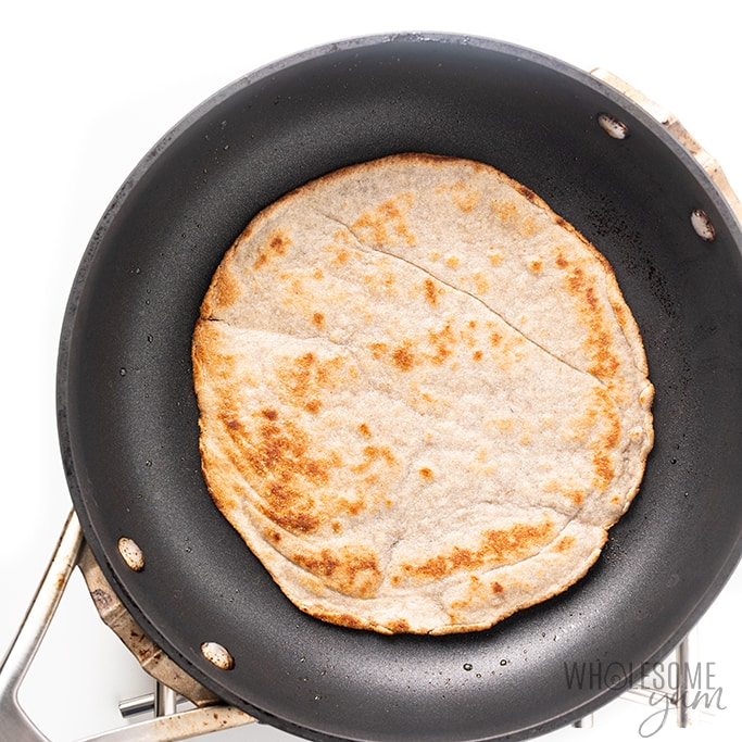 keto tortillas being cooked in a pan