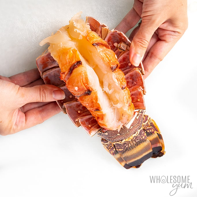 pulling lobster meat out from shell with hands