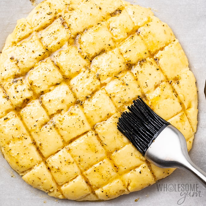 brushing butter over keto cheese bread with almond flour