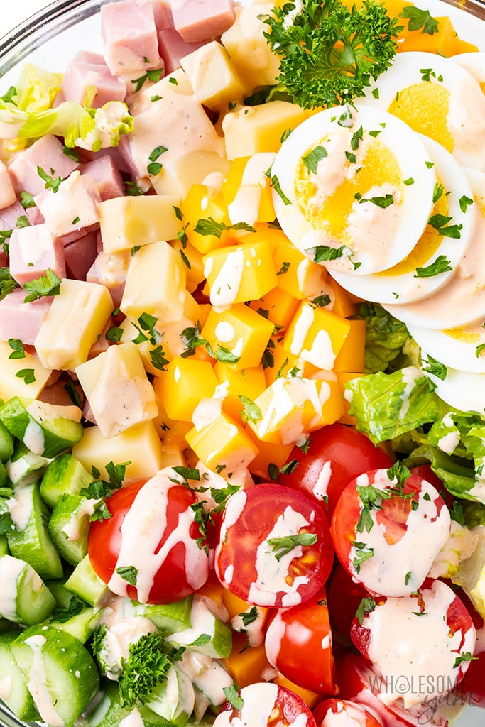 homemade chef salad with dressing drizzled on top - closeup picture