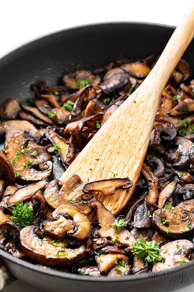 Close-up image of sauteed garlic mushrooms in a pan with a spoon