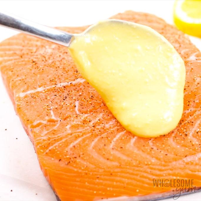 spooning sauce over lemon garlic salmon